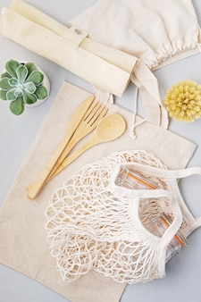 Zero waste concept. set of eco friendly bamboo cutlery, mesh cotton bag, reusable coffee tumbler. sustainable, ethical shopping, plastic free lifestyle. top view, flat lay.