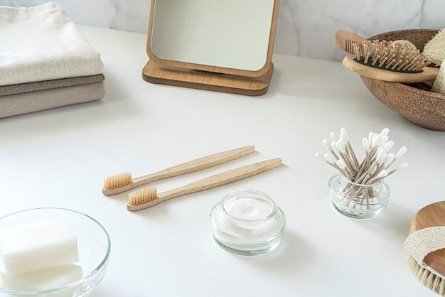 ゼロウェイストのコンセプト。環境にやさしいバスルームアクセサリーのセット-竹の歯ブラシ、綿棒、天然のヘアブラシ、鏡、リネンのナプキン。持続可能なライフスタイル。