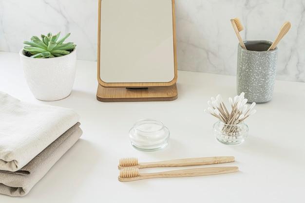 ゼロウェイストのコンセプト。白いテーブルの上の環境に優しいバスルームアクセサリーのセット