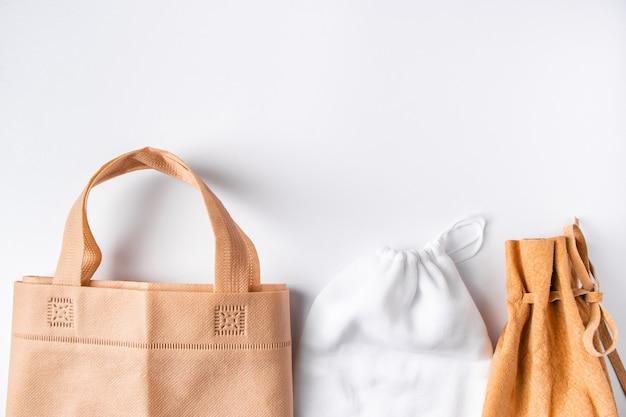 ゼロウェイストのコンセプト。リサイクルされた家庭用アクセサリーのセット-環境に優しいバッグ、ガラス、木製用品