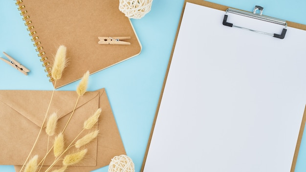 Zero waste concept. white sheet on clipboard, craft envelopes on a bright blue