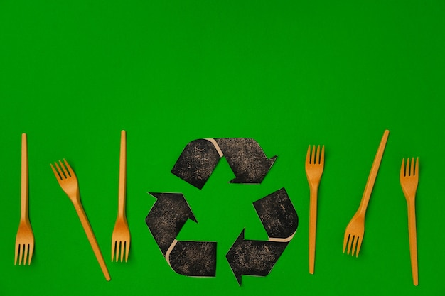 Zero waste disposable tableware forks on green background, top view