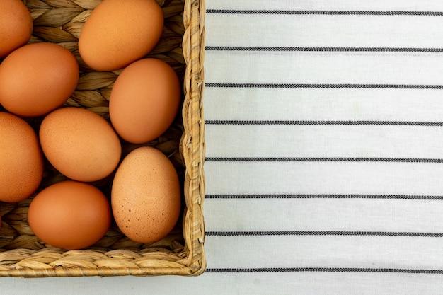 Нулевые отходы пасхального фона. никакой пластиковой концепции. минималистичный стиль. коробка бежевого водного гиацинта с коричневыми куриными яйцами на текстильном фоне.