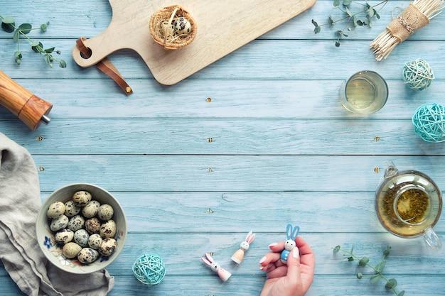 Нулевые отходы пасхального фона на синем деревянном столе. перепелиные пасхальные яйца и натуральное весеннее украшение