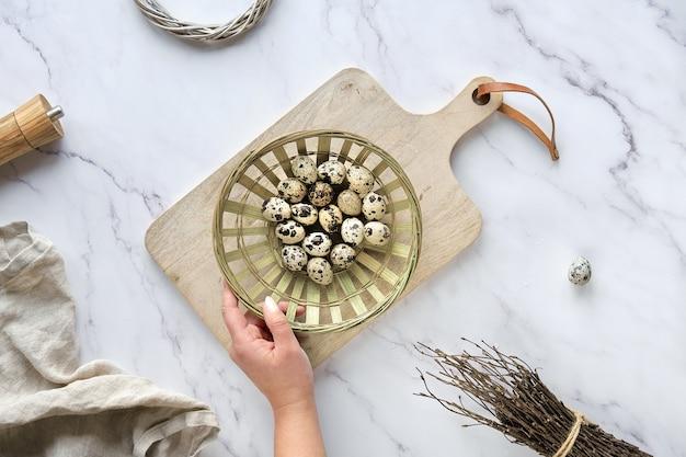 大理石のテーブルにゼロ廃棄物のイースターの背景。ウズラのイースターエッグと春の自然の飾りとユーカリの小枝。