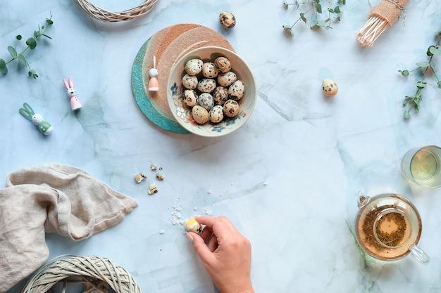 Нулевые отходы пасхального фона на мраморном столе. перепелиные пасхальные яйца и натуральные весенние украшения и веточки эвкалипта.