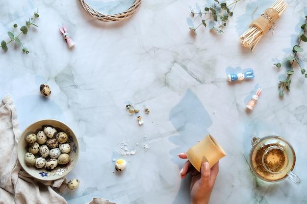 Нулевые отходы пасхального фона на мраморном столе. перепелиные пасхальные яйца и натуральные весенние украшения, веточки и эвкалипт.
