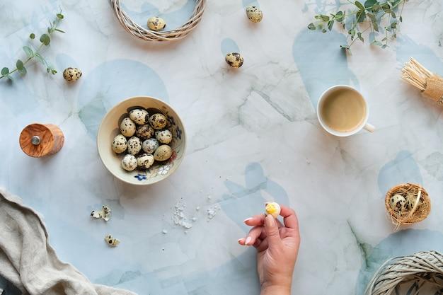 大理石のテーブルにゼロ廃棄物のイースターの背景。ウズラのイースターエッグと春の自然の装飾、小枝、ユーカリ。