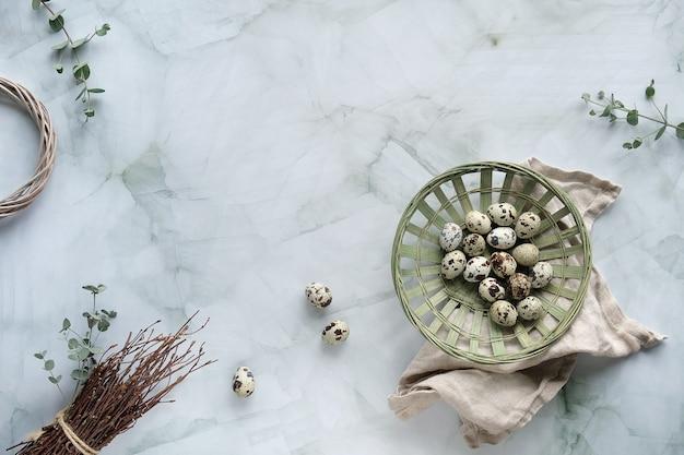 大理石のテーブルにゼロ廃棄物のイースターの背景。ウズラのイースターエッグと春の自然の飾り