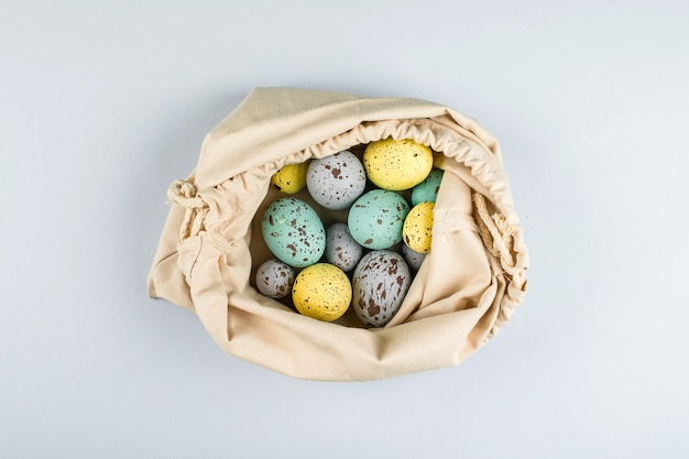 Zero waste easter concept. colorful pastel easter eggs in textile bag on grey background. top view, flat lay, copy space