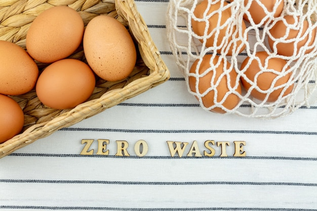 ゼロウェイストイースターのコンセプト。ビニール袋のコンセプトはありません。最小限のスタイル。テキスタイルの背景に茶色の鶏の卵とベージュのメッシュのショッピングバッグ。