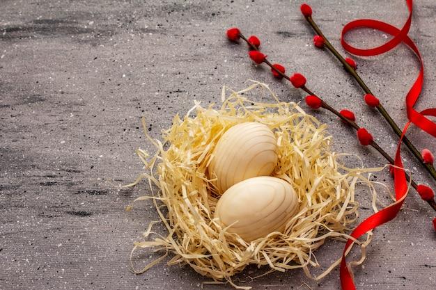 廃棄物のないイースターのコンセプト。木製の卵、鳥の巣、サテンのリボン、赤い柳のシール。プラスチックなし、エコトレンド。灰色のコンクリートの背景