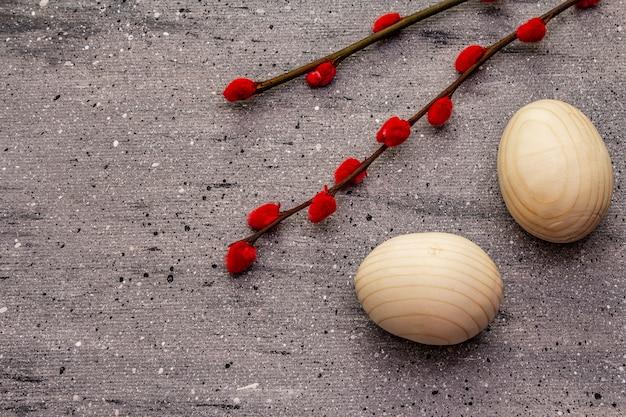 廃棄物のないイースターのコンセプト。木製の卵、サテンのリボン、赤い柳のシール。プラスチックなし、エコトレンド。灰色のコンクリートの背景