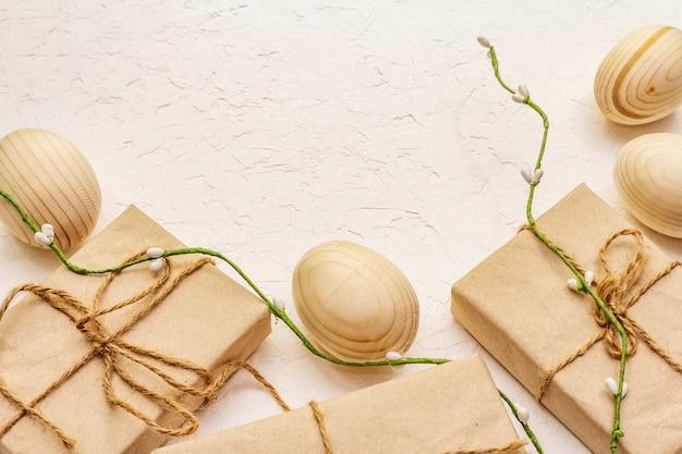 廃棄物のないイースターのコンセプト。木製の卵、クラフト紙のギフト。プラスチックではなく、エコトレンド。白いパテの背景