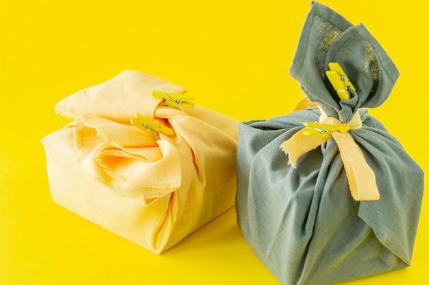 폐기물 제로, 일본 전통 후로시키 스타일의 친환경 선물 포장, 환경 개념, 친환경 배너. 2021년 트렌드 컬러 일루미네이팅 옐로우와 얼티밋 그레이.