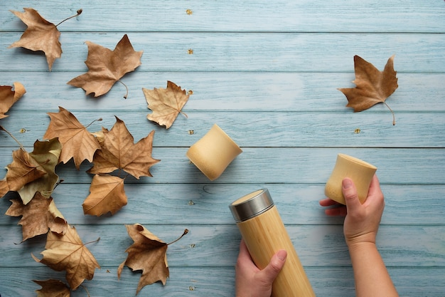 Zero waste eco friendly insulated bamboo flask with bamboo cups. trendy flat lay with hands holding the flask and natural bamboo cup on aged blue mint wooden table with autumn sycamore leaves.