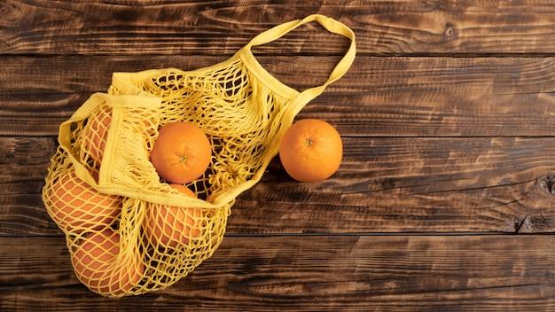 コピースペースのある木製の壁に果物が付いた廃棄物ゼロのエコショッピングバッグ。オレンジのエコバッグ。社会環境責任の概念。