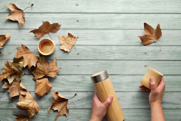 Zero waste flat lay. trendy flat lay with hands holding the flask and natural bamboo cup on wood with autumn leaves