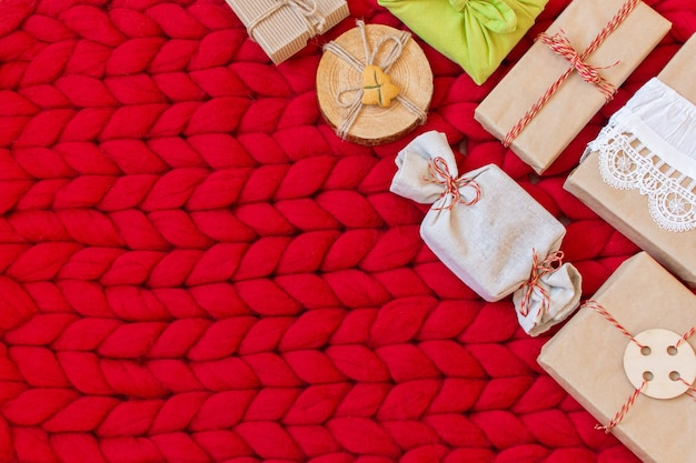 Zero waste gift boxes on a soft hand knitted merino wool blanket  hand crafted gifts with natural xmas decorationsw rapping craft paper