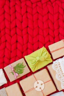 Zero waste gift boxes wrapping in traditional japanese furoshiki style on a soft hand knitted merino wool blanket hand crafted gifts with natural xmas decorationsw rapping craft paper