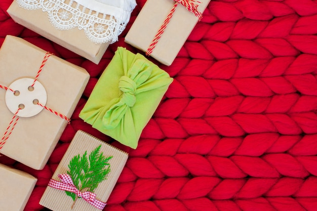 Zero waste gift boxes wrapping in traditional japanese furoshiki style on a soft hand knitted merino wool blanket hand crafted gifts with natural xmas decorationsw rapping craft