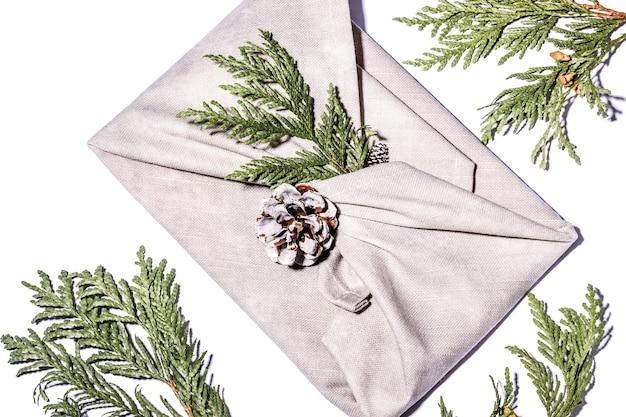 日本の伝統的な風呂敷スタイルを包むゼロウェイストギフト。クリスマス用のベージュの手作りギフトパッケージ。生地、クロベ、コーンが白になっています。エコロジーコンセプト環境にやさしい装飾クリスマス。閉じる。