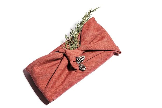 日本の伝統的な風呂敷スタイルを包むゼロウェイストギフト。生地のthujaと白で隔離されたコーンを備えたクリスマスの手作りギフトパッケージ。エコロジーコンセプト環境にやさしい装飾クリスマス。