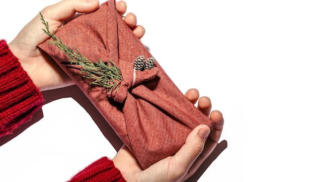 伝統的な和風のラッピングゼロウェイストギフト。子供の手は、白で隔離された生地のクロベとコーンでクリスマスのギフトパッケージを提供します。エコロジーコンセプト環境にやさしい装飾クリスマス。