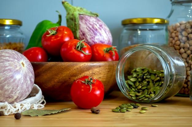 ゼロウェイスト健康食品-穀物、種子、野菜フラットは灰色の背景に横たわっていた。テキスタイルバッグ、ガラス瓶、木製ボウルの食料品。環境にやさしいプラスチックフリーの低廃棄物ライフスタイル。