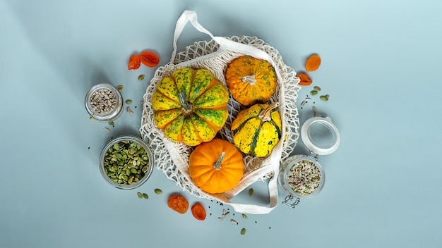 Zero waste healthy food pumpkin, seeds, vegetables, dried fruits flat lay on blue background. groceries in textile bags,glass jars. eco friendly plastic free low waste lifestyle.