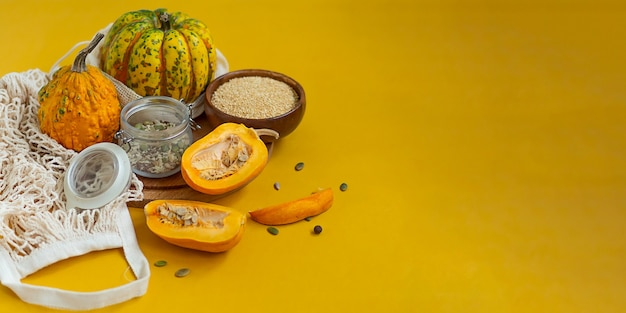 Zero waste healthy food pumpkin, seeds, vegetables, dried fruits flat lay on orange background. groceries in textile bags,glass jars. eco friendly plastic free low waste lifestyle.