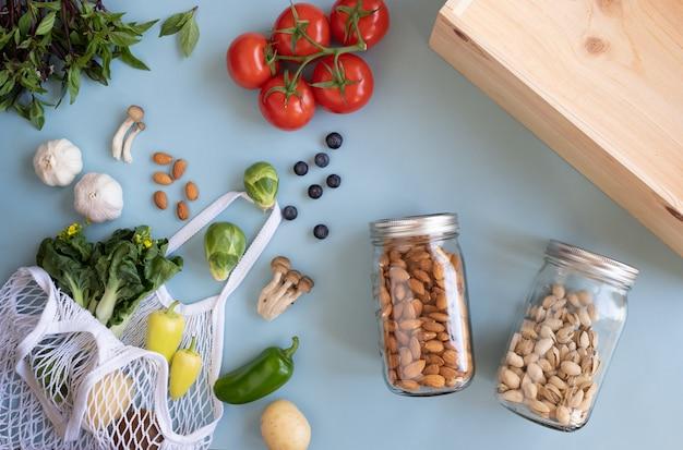 Безотходный образ жизни. хлопчатобумажная сетчатая сумка со свежими овощами и устойчивой стеклянной банкой на синей поверхности.
