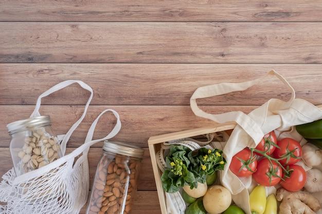 Ноль отходов жизни. хлопок сетчатая сумка со свежими овощами на деревянном столе плоской планировки. без пластика для покупки продуктов и доставки.