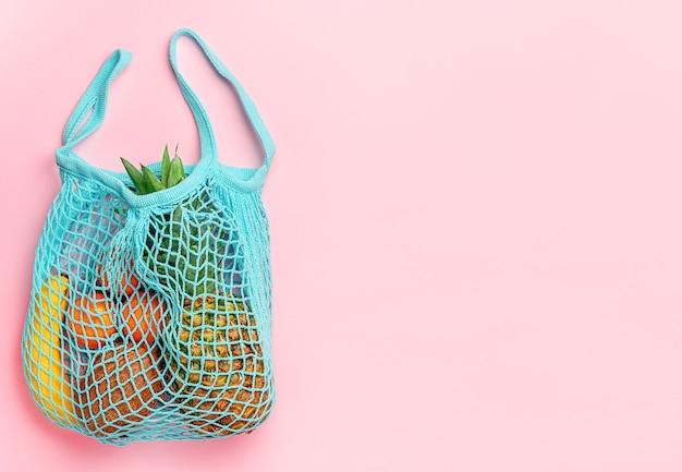 Образ жизни без отходов. различные фрукты в многоразовой хозяйственной сумке на розовом фоне. прямо вверху скопируйте пробел.