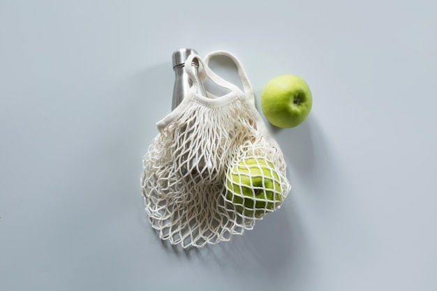 Zero waste. modern shopping net bag with apples and bottle.