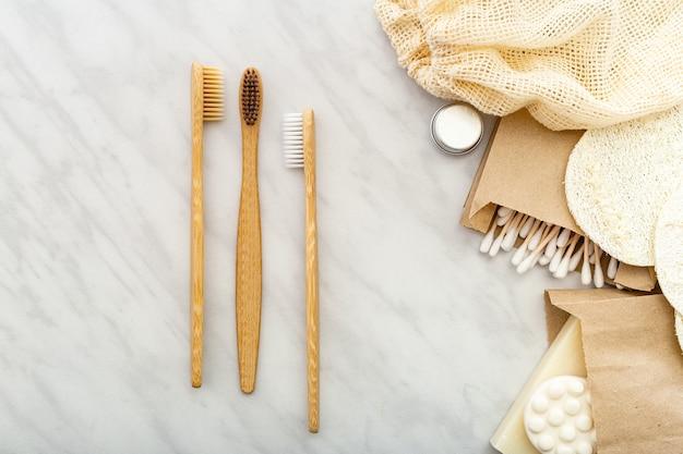 Безотходный натуральный продукт для ванны. бамбуковые зубные щетки, мыло ватные тампоны деревянные палочки, мочалки из люфы на белом мраморном фоне. плоское пространство для копирования. экологичность, без отходов, без пластика стоматологическая помощь