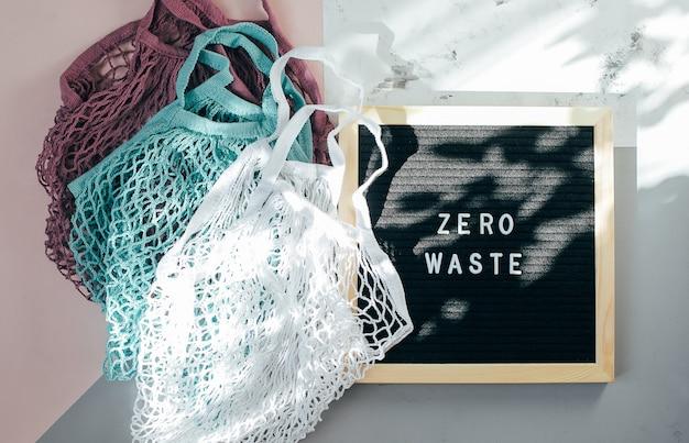 Две многоразовые хлопчатобумажные сумки (сетчатые мешки) и доска с черными буквами с надписью zero waste on