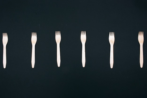 Zero waste. plastic free. eco friendly natural wooden forks in the row on dark, top view.
