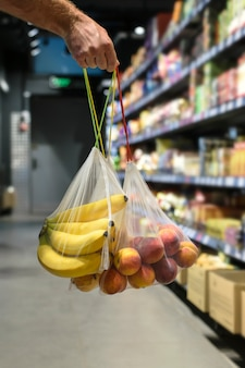 Zero waste, plastic free recycled  produce bag for carrying fruit.fruit in hand in reusable grocery mash in shop