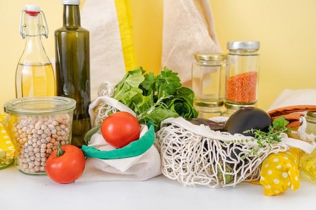 Многоразовая вощеная ткань без отходов, хлопковые пакеты, стеклянные бутылки на кухне. овощи. устойчивый образ жизни. яркий светящийся желтый фон. положительные цвета