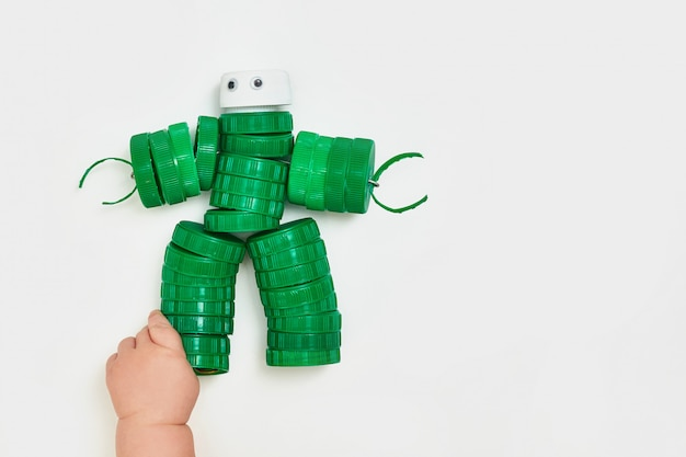 Zero waste, the second life of things. toy robot made of plastic caps on a white background. faceless. recycling art.