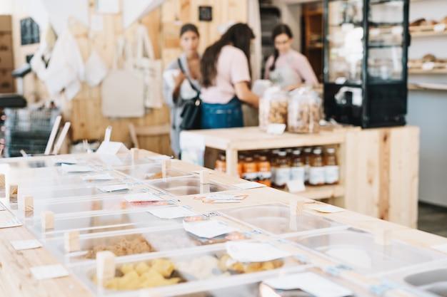 플라스틱 없는 식료품점에서 건조 제품 및 벌크 제품을 구매하는 제로 폐기물 매장 고객