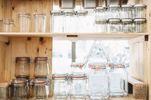 제품 구매 및 보관을 위한 다양한 재사용 가능한 유리 병이 있는 제로 폐기물 상점 나무 선반
