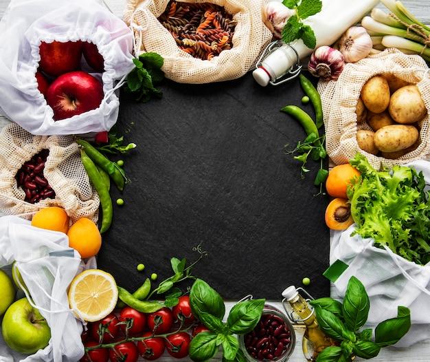 ゼロウェイストショッピングと持続可能なライフスタイルのコンセプト、再利用可能なパッケージのスーパーマーケットバッグに入ったさまざまな農場の有機野菜、穀物、パスタ、果物。コピースペース上面図、黒の背景