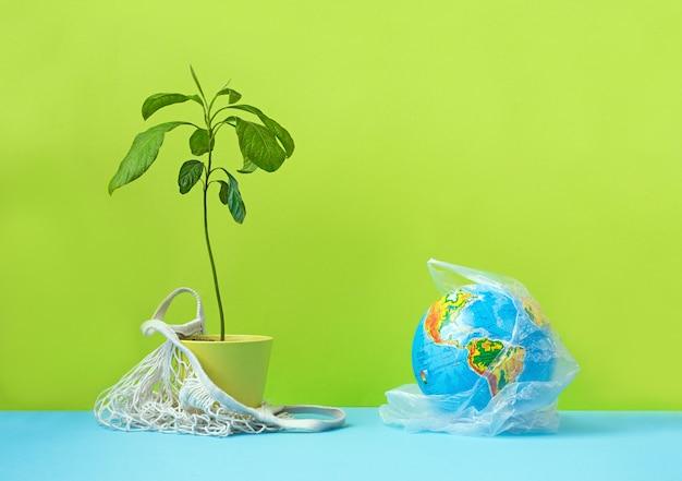 廃棄物ゼロのショッピングコンセプト。黄色の背景に綿の袋に緑の植物