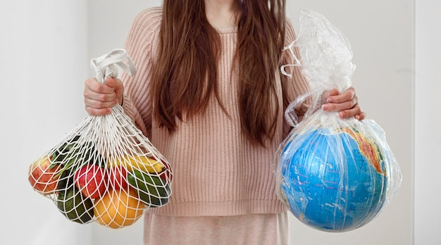 Zero waste shopping concept. woman holding in one hand reusable eco bag with vegetables and in other globe in plastic polyethylene bag