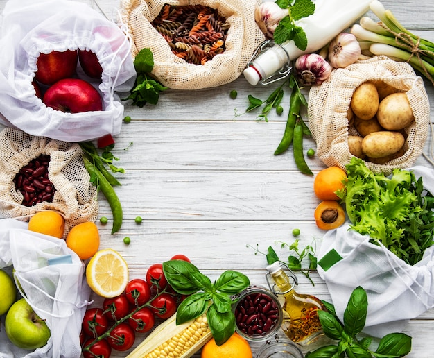 Zero waste shopping and sustanable lifestyle concept, various farm organic vegetables, grains, pasta and fruits in reusable packaging supermarket bags. copy space top view, wooden background