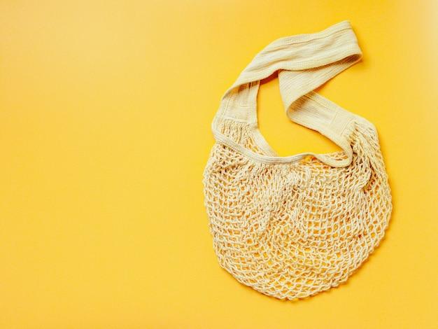 Отсутствие отходов, экологичный образ жизни, концепция без пластика. экологичный натуральный сетчатый мешок на желтом фоне.