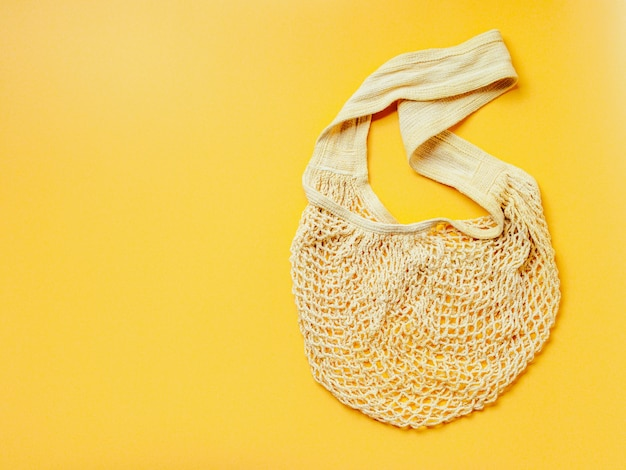 Zero waste, sustainable lifestyle, plastic free concept. eco friendly natural mesh bag on yellow background.