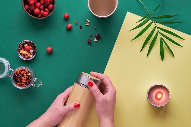 Zero waste tea to go, making herbal infusion in eco friendly insulated bamboo steel flask with herbal mixture and fresh cranberry. trendy creative flat lay with hands, two tone green and yellow paper.